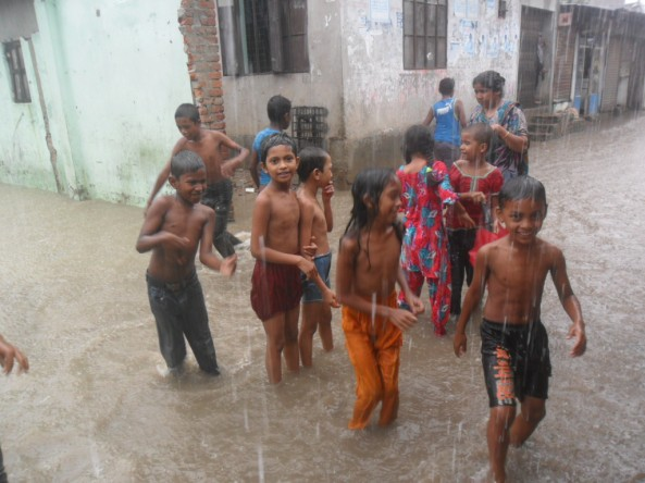 Children playing in a monsoon in the Amarok Society work area in the city of Dhaka